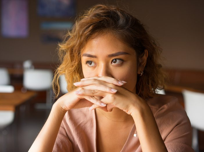 Closeup of worried young Asian woman at cafe covering nose and mouth with clasped hands.