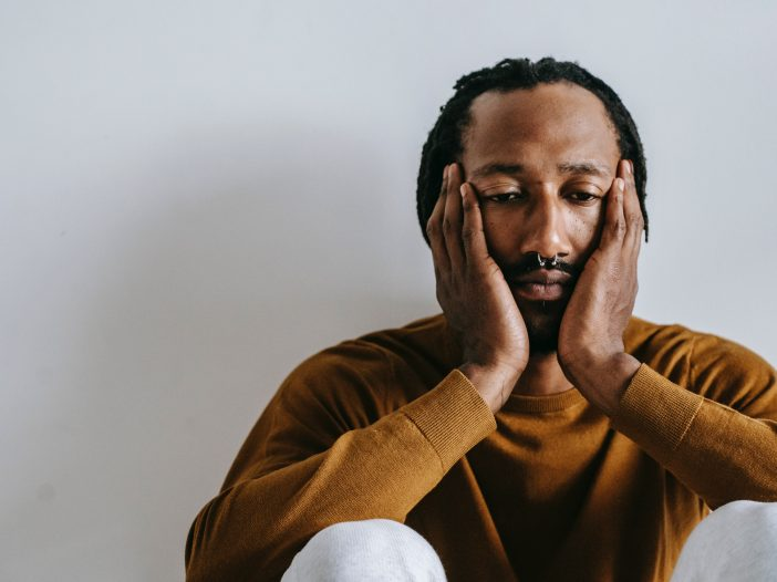 Closeup of a sad young black man with a septum piercing sitting against a wall, head in his hands.