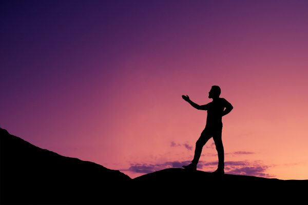 Silhouette of a person on a hill at sunset with their arm raised. The sky behind them is vibrant shades of purple, pink, and orange.